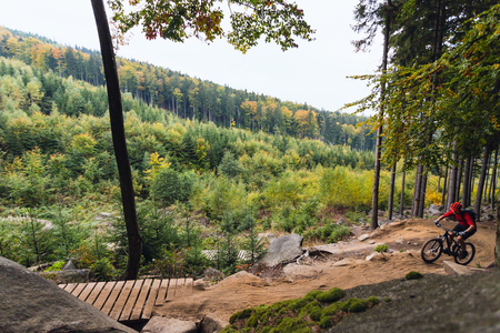 bike trail: Mountain biker riding on bike in autumn inspirational mountains landscape. Man cycling MTB on enduro trail track. Sport fitness motivation and inspiration.