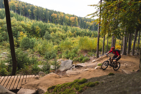 trails: Mountain biker riding on bike in autumn inspirational mountains landscape. Man cycling MTB on enduro trail track. Sport fitness motivation and inspiration.