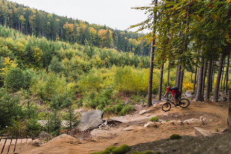 cycling: Mountain biker riding on bike in autumn inspirational mountains landscape. Man cycling MTB on enduro trail track. Sport fitness motivation and inspiration.