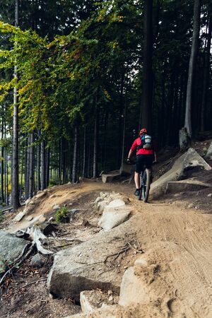 fitness motivation: Mountain biker riding on bike in autumn inspirational mountains landscape. Man cycling MTB on enduro trail track. Sport fitness motivation and inspiration.