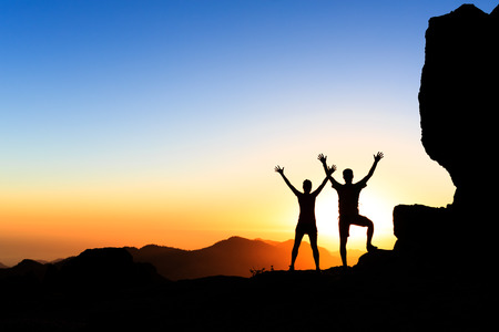 accomplish: Couple hikers success in sunset mountains, accomplish with arms up outstretched. Young man and woman on rocky mountain range looking at beautiful inspirational landscape view, Gran Canaria Canary Islands. Stock Photo