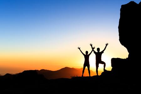 Paar wandelaars succes in zonsondergang bergen, te bereiken met de armen omhoog uitgestrekte. Jonge man en vrouw op rotsachtige bergen op zoek naar mooie inspirerende landschap uitzicht, Gran Canaria Canarische Eilanden. Stockfoto