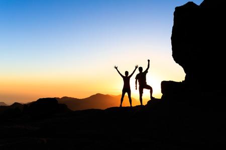 Man en vrouw wandelaars wandelen in de zomer bergen, te bereiken met uitgestrekte armen. Jong stel op rotsachtige bergen op zoek naar mooie inspirerende landschap uitzicht, Gran Canaria Canarische Eilanden.