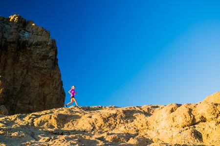 corriendo: Mujer que se ejecuta en las montañas rocosas, la formación y el trabajo en el hermoso paisaje inspirador montaña. Fitness y ejercicio, campo a través del corredor de footing. Foto de archivo