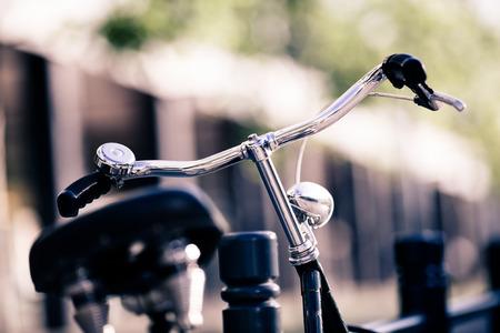 bicyclette: Vintage vieux v�lo de ville color�e r�tro lumi�re et le guidon sur la rue, le transport de l'�cologie alternative trajet � v�lo classique en milieu urbain, floue belle bokeh. mise au point s�lective sur le guidon.