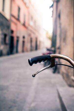 urban colors: Ciudad vieja manillar de la bicicleta y la cesta sobre fondo borroso bokeh hermosa en calle de la ciudad de Europa. Vintage moto de estilo retro con espacio de copia bokeh. Enfoque selectivo en el manillar. Foto de archivo