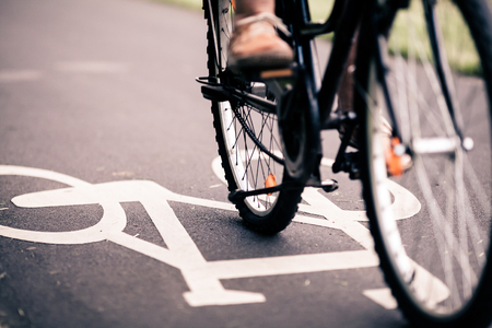 City bicycle riding on bike path, alternative ecological transportation. Commute on bicycle in urban environment, asphalt gray bike lane with bicycle markings Фото со стока