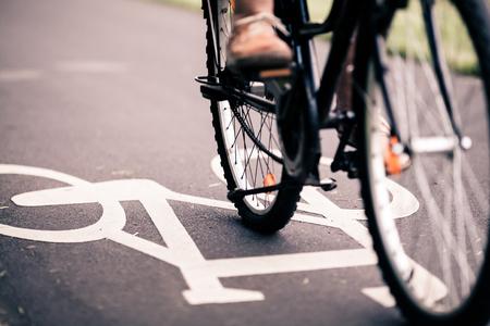Stadt Fahrrad fahren auf Radweg, alternative ökologische Transport. Arbeitsweg mit dem Fahrrad in der städtischen Umgebung, asphaltgrau Radweg mit dem Fahrrad Markierungen Lizenzfreie Bilder