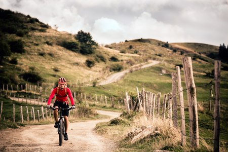 trails: Mountain biker riding on bike in summer mountains landscape. Man cycling MTB on rural country road. Sport fitness motivation and inspiration.