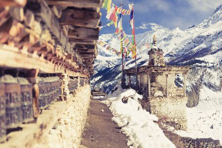 village: Prayer wheels in high Himalaya Mountains, Nepal village. Focus on the stupa and prayers flags. Annapurna Two range region in Nepal, located at Annapurna Circuit Trekking Hiking Trail