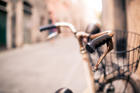 europe vintage: City old bicycle handlebar and basket over blurred beautiful bokeh background on Europe city street. Vintage retro style bike with bokeh copy space. Selective focus on handlebar. Stock Photo