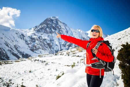 healthy looking: Woman hiker walking, looking and pointing at beautiful inspirational winter mountains. Trekking and hiking inspiration and motivation in beautiful landscape. Travel and healthy lifestyle outdoors on snow in Himalayas, Nepal. Stock Photo