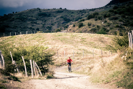 fitness motivation: Mountain biker riding on bike singletrack trail in autumn mountains. Man rider cycling MTB on rural country road or single track. Sport fitness motivation and inspiration in beautiful inspirational landscape.
