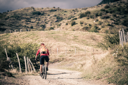 road cycling: Mountain biker riding on bike singletrack trail in autumn mountains. Man rider cycling MTB on rural country road or single track. Sport fitness motivation and inspiration in beautiful inspirational landscape.