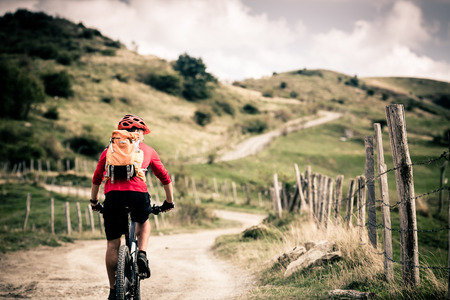 Mountain biker riding on bike singletrack trail in autumn mountains. Man rider cycling MTB on rural country road or single track. Sport fitness motivation and inspiration in beautiful inspirational landscape.