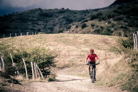 mountain road: Mountain biker riding on bike singletrack trail in autumn mountains. Man rider cycling MTB on rural country road or single track. Sport fitness motivation and inspiration in beautiful inspirational landscape.