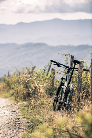 fitness motivation: Mountain bike resting on a fance singletrack trail in autumn mountains. Cycling MTB on rural country road or single track. Sport fitness motivation and inspiration in beautiful inspirational landscape.