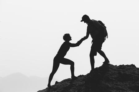 ayudando: Pareja de trabajo en equipo mano amiga, la confianza, la ayuda de la silueta en las montañas, puesta del sol. Personas de los escaladores hombre y mujer excursionistas, se ayudan mutuamente en la cima de la montaña, escalar juntos, hermoso paisaje inspirador