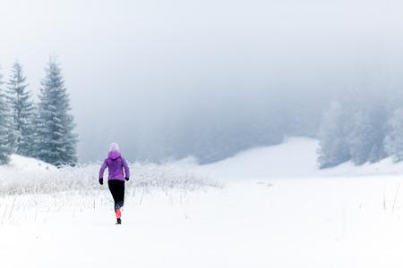 corriendo: Invierno Funcionamiento de la mujer. Deporte, fitness, la inspiración y la motivación para correr. Campo a través de la mujer joven feliz corriendo en las montañas de nieve, día de invierno. Corredor de pista femenino que se resuelve, trotar ejercicio. Foto de archivo