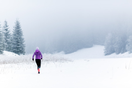 girl jogging: Winter running woman. Sport, fitness, jogging inspiration and motivation. Young happy woman cross country running in mountains on snow, winter day. Female trail runner working out, jogging exercising.