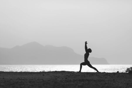 meditation isolated white: Woman meditating in yoga pose silhouette at the ocean, beach and mountains. Motivation and inspirational exercising. Healthy lifestyle outdoors in nature, fitness concept.