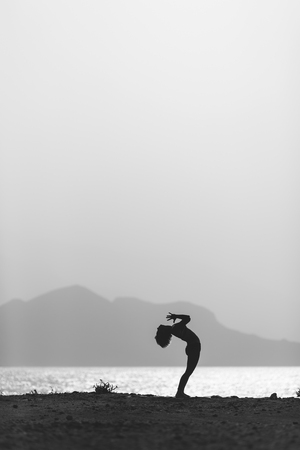 human silhouette: Woman meditating in yoga pose silhouette at the ocean, beach and mountains. Motivation and inspirational exercising. Healthy lifestyle outdoors in nature, fitness concept.