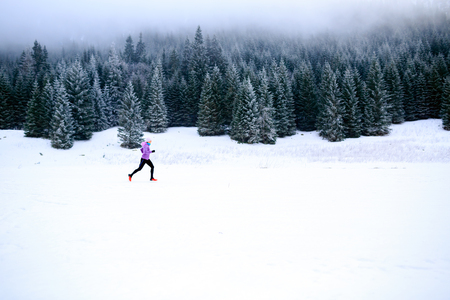 trails: Winter running woman. Sport, fitness, jogging inspiration and motivation. Young happy woman cross country running in mountains on snow, winter day. Female trail runner working out, jogging exercising.