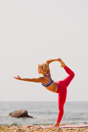 yoga: Woman meditating in yoga pose, exercise on the beach. Motivation and inspirational exercising. Healthy lifestyle outdoors in nature, fitness concept. Stock Photo