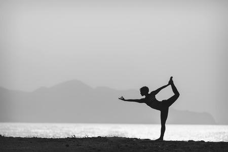 Vrouw mediteren in yoga stelt silhouet op de oceaan, het strand en de bergen. Motivatie en inspirerende oefenen. Zwart-wit foto met een gezonde levensstijl buiten in de natuur, fitness concept.