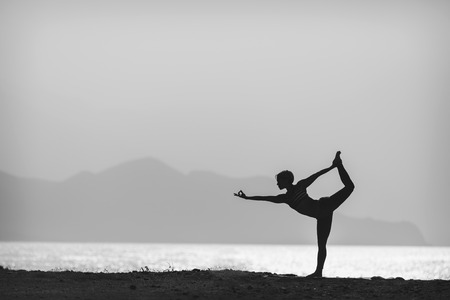 yoga pose: Woman meditating in yoga pose silhouette at the ocean, beach and mountains. Motivation and inspirational exercising. Black and white photo with healthy lifestyle outdoors in nature, fitness concept.
