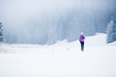 run out: Winter running woman. Sport, fitness, jogging inspiration and motivation. Young happy woman cross country running in mountains on snow, winter day. Female trail runner working out, jogging exercising.