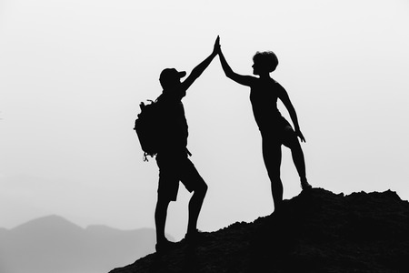 goal achievement: Successful couple achievement climbing or hiking, business concept with man and woman celebrating with arms up raised outstretched outdoors