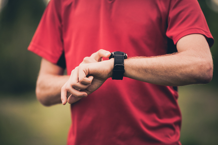 runners: Runner using heart rate monitor training running, smartwatch checking performance or GPS. Man athlete looking at stopwatch. Healthy runner closeup on trail running workout. Wearable technology for tracking activity. Stock Photo