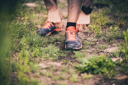 motivational: Runner tying sports shoe. Man running on cross country path in summer nature. Young athlete male training and doing fitness workout outdoors. Stock Photo