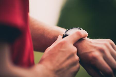 Corredor usando cardíaca de entrenamiento consecutivo monitor de ritmo, SmartWatch comprobar el rendimiento o GPS. Hombre atleta mirando cronómetro. Corredor saludable de cerca en ejercicio trail running. Tecnología usable para la actividad de seguimiento.