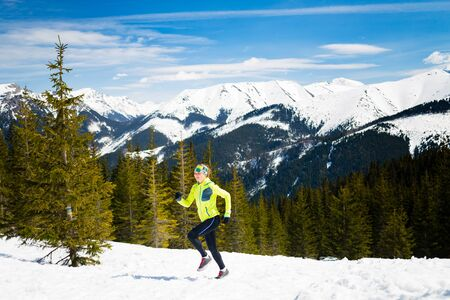 power walking: Trail running woman runner in winter mountains on snow. Motivation and inspiration fitness concept with beautiful inspirational landscape. Active accomplish runner or hiker power walking outdoors in nature. Stock Photo