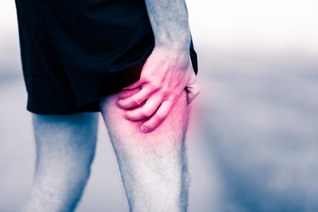 masaje deportivo: Dolor Runners pierna en entrenamiento. Hombre que sostiene el m�sculo de la pierna dolorida y dolorosa, esguince o dolor de calambre lleno de rojo rosa lugar luminoso. Persona sobreentrenamiento heridos al hacer ejercicio o correr al aire libre. Foto de archivo