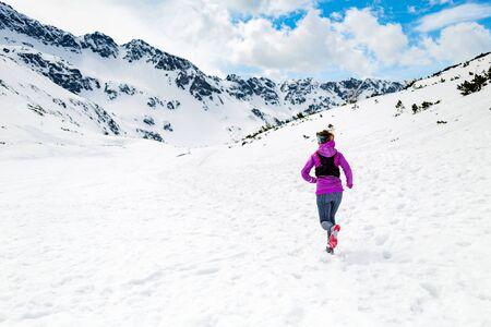 inspiración: Rutas carrera corredor de la mujer en las monta�as de invierno blanco en la nieve. La motivaci�n y la forma f�sica inspiraci�n concepto con el hermoso paisaje inspirador. Activo lograr la formaci�n corredor al aire libre en la naturaleza.
