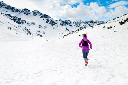run out: Trail running woman runner in white winter mountains on snow. Motivation and inspiration fitness concept with beautiful inspirational landscape. Active accomplish runner training outdoors in nature. Stock Photo