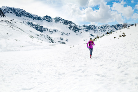 accomplish: Trail running woman runner in white winter mountains on snow. Motivation and inspiration fitness concept with beautiful inspirational landscape. Active accomplish runner training outdoors in nature. Stock Photo