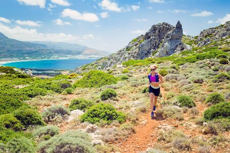 run out: Trail running woman cross country runner in mountains on summer beautiful day. Fitness training and working out runner jogging and exercising outdoors in nature, motivation and inspiration.