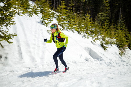 trails: Trail running woman runner in winter mountains on snow. Motivation and inspiration fitness concept with beautiful inspirational landscape. Active accomplish runner or hiker power walking outdoors in nature. Stock Photo