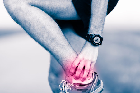 Ankle leg pain, man holding sore and painful foot muscle, sprain or cramp ache filled with red pink bright place. Overtrained injured person when training exercising or running outdoors. Stock Photo