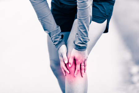 Runners knee leg pain, woman holding sore and overtrained painful knee, sprain or cramp ache filled with red pink bright place. Overtraining injured person when exercising or running outdoors. Stock Photo