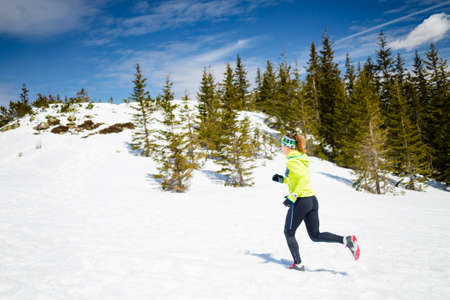 outdoors: Trail running woman runner in winter mountains on snow. Motivation and inspiration fitness concept with beautiful inspirational landscape. Active accomplish runner or hiker power walking outdoors in nature. Stock Photo