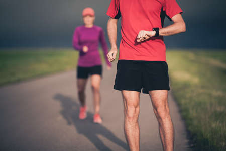 sports training: Man and woman runners running on country road in summer sunset. Young training and doing workout outdoors in nature. Checking performance on stopwatch smart watch.