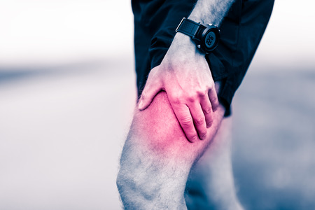 Runners leg pain, man holding sore and overtrained painful leg muscle, sprain or cramp ache filled with red pink bright place. Injured overtrained person when exercising or running outdoors. Stock Photo
