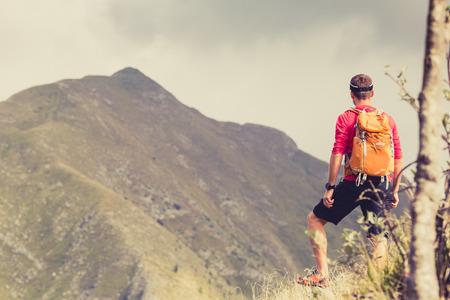 inspiración: Senderismo hombre, mochilero, escalador o corredor de pista en las montañas en busca hermosa vista del paisaje inspirador. Fitness y estilo de vida saludable al aire libre en la naturaleza del verano Foto de archivo