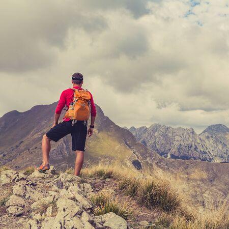 estilo de vida saludable: Senderismo hombre, mochilero, escalador o corredor de pista en las montañas en busca hermosa vista del paisaje inspirador. Fitness y estilo de vida saludable al aire libre en la naturaleza del verano Foto de archivo