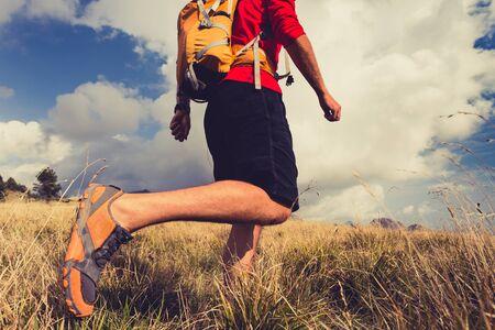 backpack: Senderismo hombre, mochilero, escalador o corredor de pista en las montañas en busca hermosa vista del paisaje inspirador. Fitness y estilo de vida saludable al aire libre en la naturaleza de verano. Foto de archivo